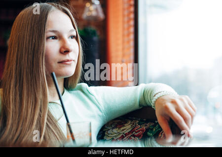 Photo of a woman drinking juice through window - Stock Photo