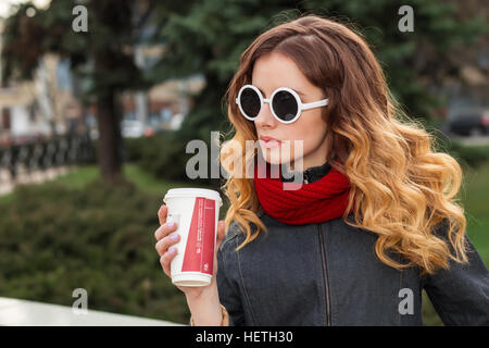 Happy young woman in sunglasses, drinking coffee outdoors. - Stock Photo