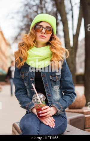 Happy young woman in sunglasses, light green cap and scarf, drinking cocktail outdoors. - Stock Photo