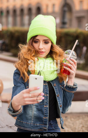 Happy young woman with a mobile phone in her hand, light green cap and scarf, drinking cocktail outdoors. - Stock Photo