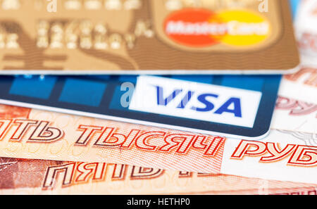 VISA and Mastercard Debit Card lying over banknotes of russian rubles - Stock Photo