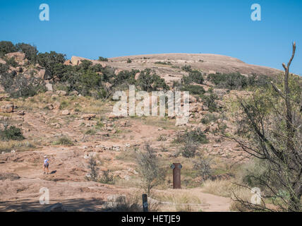 Lone hiker descends Summit Trail to top of Enchanted Rock. Trail marker at bottom of image. - Stock Photo