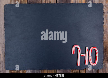 Holiday candy cane text HO on dark stone board and wooden background. Top view, flat lay. - Stock Photo