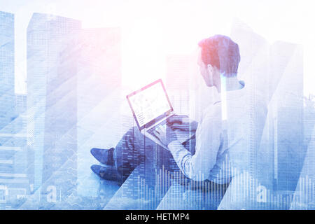 Double exposure of a businessman using a laptop computer with stock market investment dashboard and financial district - Stock Photo