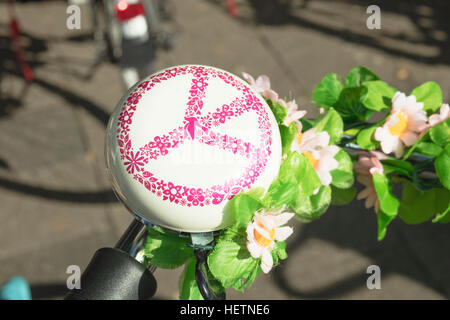 Detail of a bicycle's rounded ring bell with sign of 'Peace' drawn on it - Stock Photo