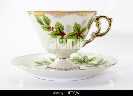 Tea cup and saucer with Christmas holly printed isolated on white - Stock Photo
