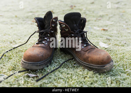 Pair of brown preloved shabby walking boots on frosty green grass - Stock Photo