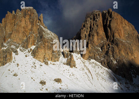 Morning light and clouds embrace Sassolungo and Sasso Piatto in the Dolomites, Santa Cristina Gherdeina, Province - Stock Photo