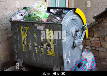 Outdoor trash bin with food waste. Not sorted garbage, yard, stench, filth - Stock Photo