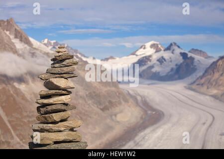 A stone cairn in the mountains in Switzerland. The Aletsch Glacier and the Eiger and Mönch mountains are visible - Stock Photo