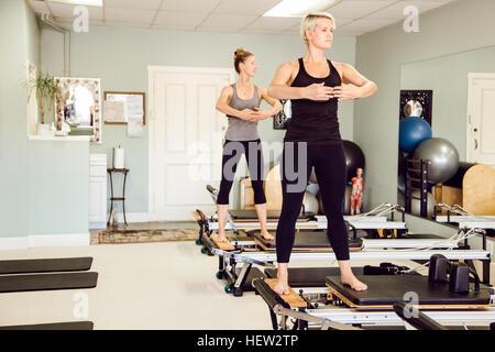 Women in gym using pilates reformer - Stock Photo
