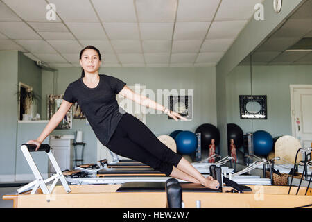 Woman in gym using pilates reformer - Stock Photo