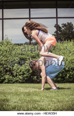 Male and female high school students playing leapfrog outside high school - Stock Photo