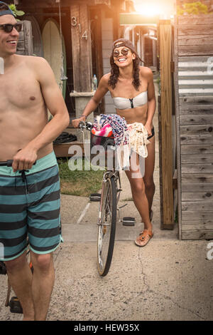 Couples pushing bicycles smiling, Rockaway Beach, New York, USA - Stock Photo