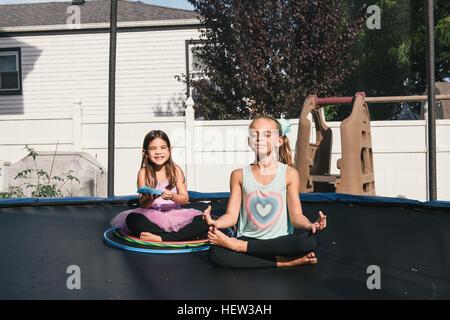 Girls sitting cross-legged on trampoline meditating - Stock Photo