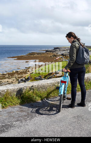 Young woman standing with bicycle beside sea wall, Inishmore, Ireland - Stock Photo