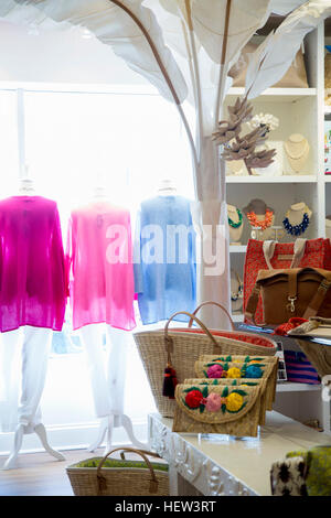 Row of colourful blouses on clothes rail in fashion boutique window - Stock Photo
