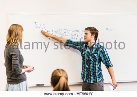 Teenage boy pointing at whiteboard in high school lesson - Stock Photo