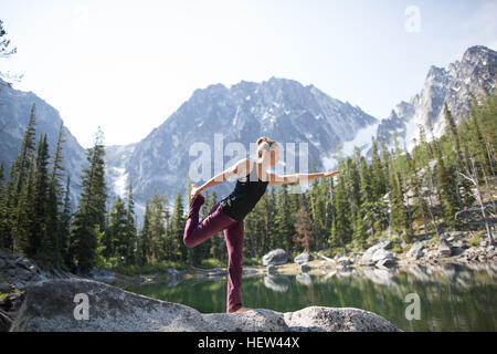 Young woman standing on rock beside lake, in yoga pose, The Enchantments, Alpine Lakes Wilderness, Washington, USA - Stock Photo