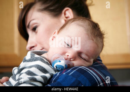 Mother holding sleeping baby boy - Stock Photo