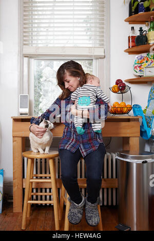 Mother holding sleeping baby boy and stroking cat - Stock Photo