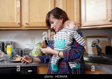 Mother holding sleeping baby boy and looking at smartphone - Stock Photo