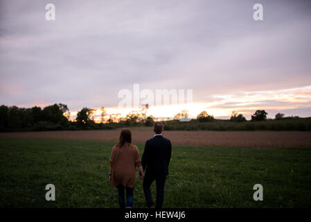 Rear view of romantic couple in field watching sunset - Stock Photo