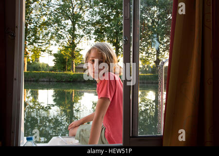 Boy sitting on side of barge, looking through window - Stock Photo