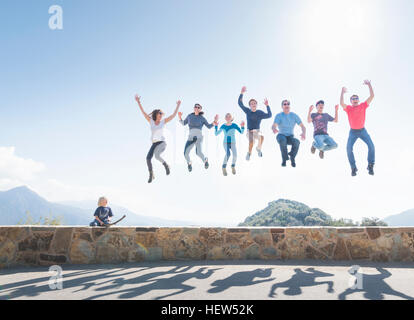Group of people jumping in air, young boy sitting on wall, Sequoia National Park, California, USA - Stock Photo