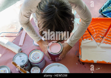 Girl in garage stirring paint in paint tins - Stock Photo