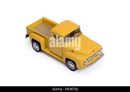 Yellow toy pickup car on white background. - Stock Photo