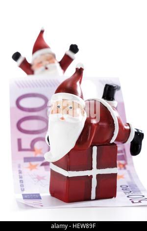 Santa Claus figure on gift with Euro bills - symbol for Christmas bonus - Stock Photo