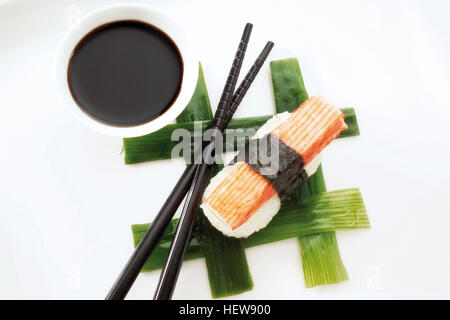 Sushi Nigiri, made with imitation crab meat and rice wrapped in nori seaweed and placed beside black chopsticks - Stock Photo