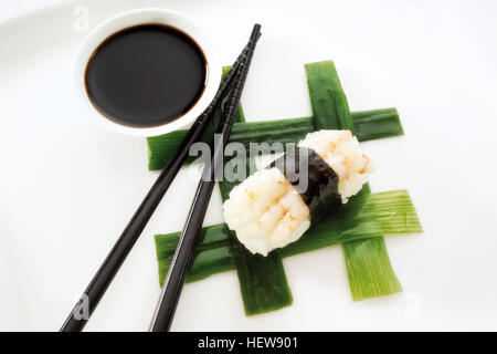 Sushi Nigiri, made with shrimp and rice wrapped in nori seaweed and placed beside black chopsticks and a bowl of - Stock Photo