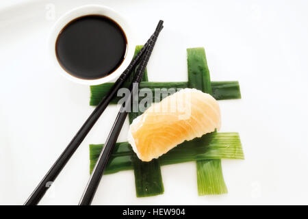 Sushi Nigiri, made with salmon and rice, placed beside black chopsticks and a bowl of soy sauce on interwoven leek - Stock Photo