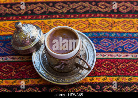 Traditional Turkish Coffee in a ceramic coffee mug covered with copper pot on tablecloth traditional texture and - Stock Photo