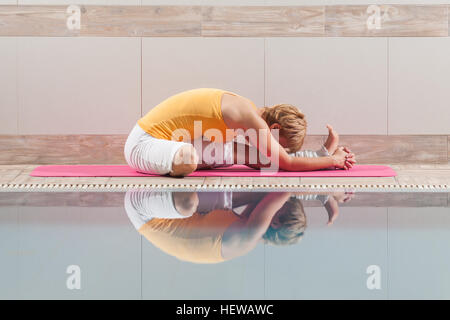 Young woman is practicing yoga. - Stock Photo