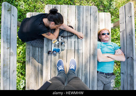 Overhead point of view shot of couple resting on picnic bench - Stock Photo