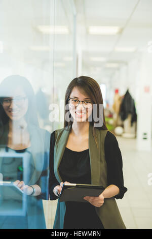 Portrait of young woman leaning against office doorway using digital tablet - Stock Photo