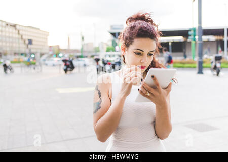 Woman in urban area using digital tablet - Stock Photo