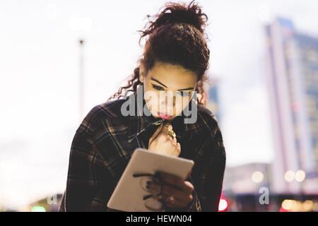 Woman in urban area using digital tablet, Milan, Italy - Stock Photo