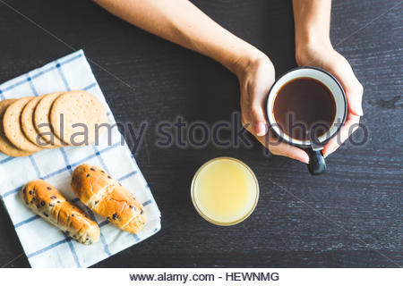 Overhead view of woman's hands holding coffee cup - Stock Photo