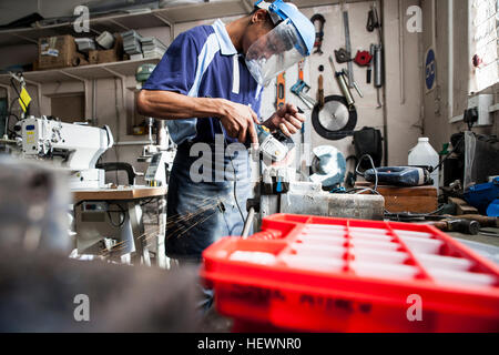 Young man using angle grinder at vice in repair workshop - Stock Photo