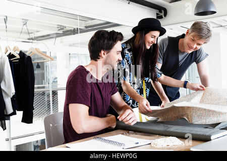 Colleagues at desk looking at folding map smiling - Stock Photo