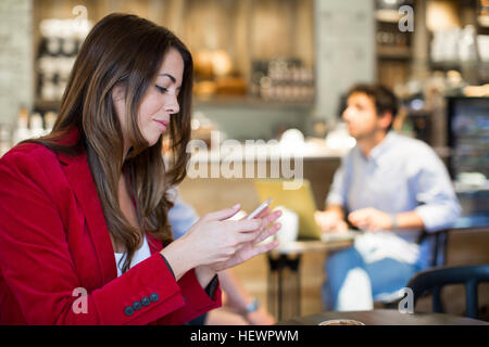Young woman reading smartphone texts in cafe - Stock Photo