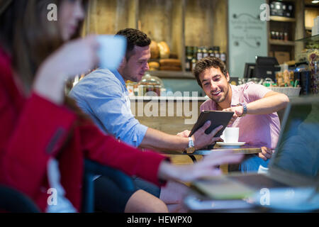 Male friends sitting in cafe pointing at digital tablet - Stock Photo