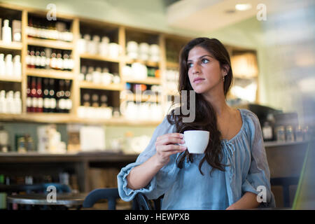 Young woman sitting in cafe looking sideways - Stock Photo