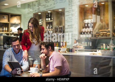 Male and female friends in cafe looking at digital tablet - Stock Photo