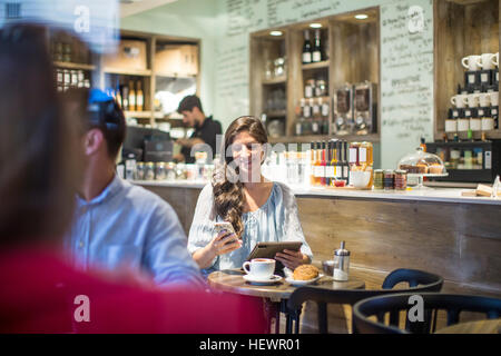 Young woman with digital tablet reading smartphone texts in cafe - Stock Photo