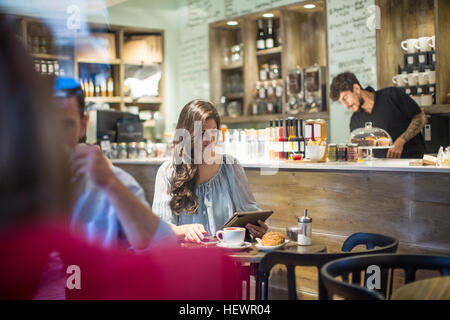 Young woman looking at digital tablet in cafe - Stock Photo